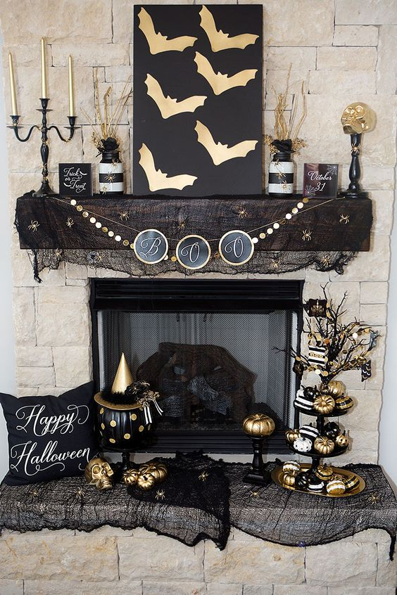 Stylish Black And Gold Fireplace Mantel Decor With A Bat Sign Candles Banners