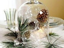 a cloche with sheer glass ornaments and pinecones plus pine needles as a centerpiece