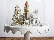 a cloche with a bead and ornament tree, tinsel trees and a white house for a vintage look