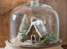 a cloche with a gingerbread house, a tinsel tree and little figurines will be a cool winter decoration