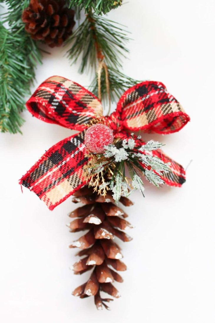 DIY pinecone ornaments with plaid ribbon bows and fake greenery and berries  (via domesticallycreative.
