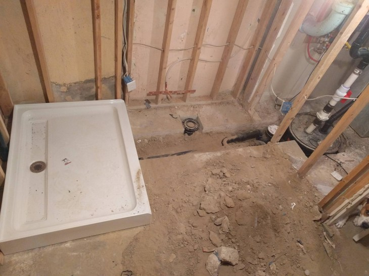 How do I pour concrete over basement plumbing?