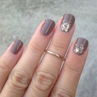 Picture Of rounded taupe nails with gold glitter touches
