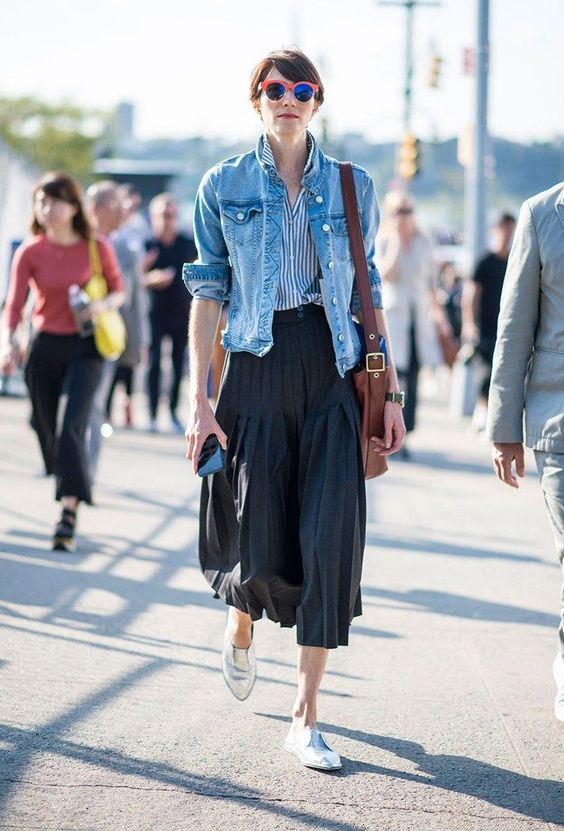 a striped shirt, a blue denim jacket, a black pleated midi and silver Oxford shoes