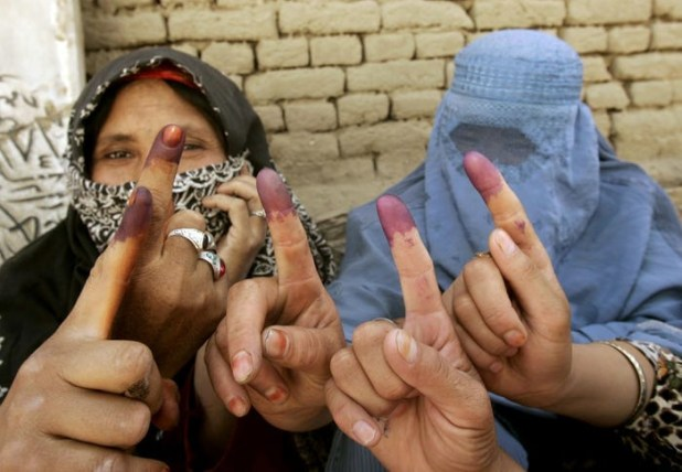 Afghan women show their inked fingers after they voted during parliamentary elections at a mosque used as a polling station in the Afghan capital Kabul, September 18, 2005. [Photo: Reuters]