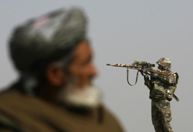 A French sniper looks through his rifle's scope while keeping watch over Qarabagh district, north of Kabul, November 20, 2007. [Photo: Reuters]