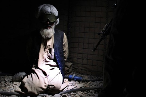 An Afghan man is detained by US Marines from the First Battalion, Eighth Marines Bravo Company at their base in Talibjan after a battle against Taliban insurgents in Musa Qala district in southern Afghanistan's Helmand province November 7, 2010. [Photo: Reuters]