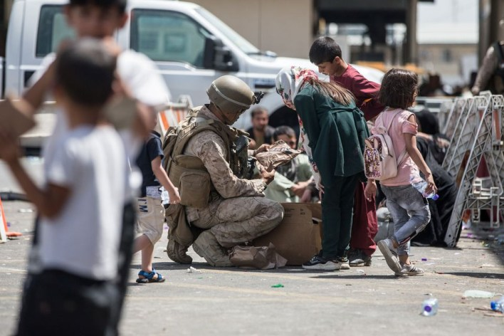 A U.S. Marine provides meals ready-to-eat to a child during an evacuation at Hamid Karzai International Airport, Kabul, Afghanistan, August 21, 2021. Picture taken August 21, 2021. U.S. Marine Corps/Sgt. Samuel Ruiz/Handout via REUTERS