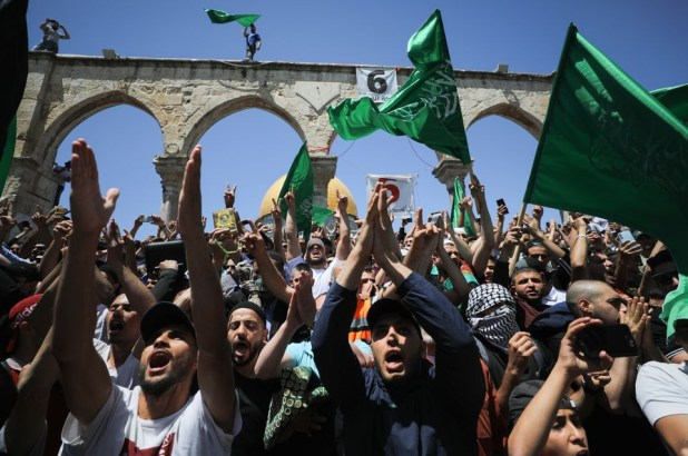 people hold hamas flags as palestinians gather after performing the last friday of ramadan to protest over the possible eviction of several palestinian families from homes on land claimed by jewish settlers in the sheikh jarrah neighbourhood in jerusalem s old city may 7 2021 reuters