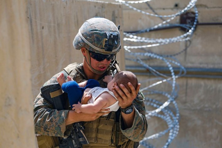 A U.S. Marine comforts an infant while they wait for the mother during an evacuation at Hamid Karzai International Airport, Afghanistan, August 21, 2021. Picture taken August 21, 2021. U.S. Marine Corps/Lance Cpl. Nicholas Guevara/Handout via REUTERS