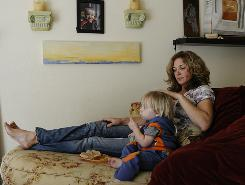 Staci Schubert and her son, Lincoln, 2, watch Curious George at her Costa Mesa, Calif., home. Schubert, who had career success and started her own business, filed for bankruptcy.