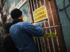 A member of the Occupy Wall Street movement places tape on a forclosed home during a march in Brooklyn Dec. 6, 2011.