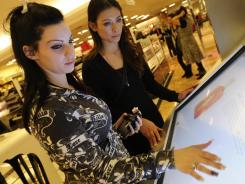 Macy's Beauty Spot concierge Sayla Ike, right, helps Eve Diaz, 22, at the interactive kiosk at the Macy's in Tysons Corner Center, in Northern Virginia. Virtual shopping experiences put online shopping in a physical environment.