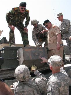 The Iraqi defense minister's top military adviser, General Mohan al-Furayji, in beige camo, inspects an M1A1 Abrams tank. Iraq is considering buying 140 of them in a deal that could be worth as much as $2.16 billion.