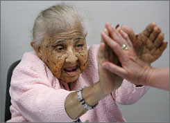 Martha Berryhill, who turned 108 on July 12, returns a high-five as she was honored a few days before by the Muscogee (Creek) Nation at a birthday party in Okmulgee, Okla. She is the last of the tribe's original allottees.