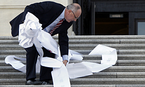 Rep. Pete Hoekstra, R-Mich., picks up a copy of the House health care bill after a rally against it on Capitol  Hill in November.