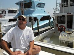 Allen Kruse beside his boat May 6 at Orange Beach, Ala. He was found dead on the boat June 23, after apparently shooting himself in the head.