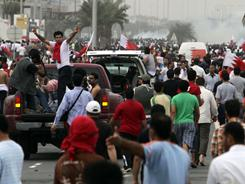 Anti-government protesters evacuate the injured to hospitals in private cars and ambulances as riot police leave the area firing tear gas Sunday in Manama, Bahrain.