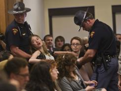 A protester is removed from a meeting of the Joint Committee on Finance at the state Capitol on Friday in Madison, Wis.