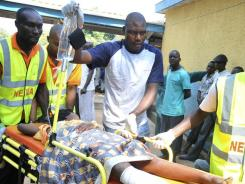 Medical officials treat a victim of a bomb blast at a Catholic church near Nigeria's capital on Sunday.