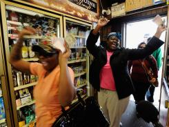 Sierra Luchien, left, and Tammy Redlen celebrate as they walk into the Bluebird Liquor store in Hawthorne, Calif., after waiting in line for nearly three hours to purchase their Mega Millions lottery ticket.