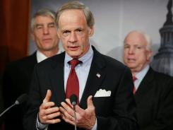 Sen. Tom Carper, center, speaks while flanked by John McCain and Sen. Mark Udall, D-Co, left, during a news conference on Feb. 8.