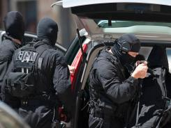 Elite police officers from the GIPN brigade arrive at a bank after a gunman took four people hostage in a bank in the southern French city of Toulouse and fired a shot, police said.