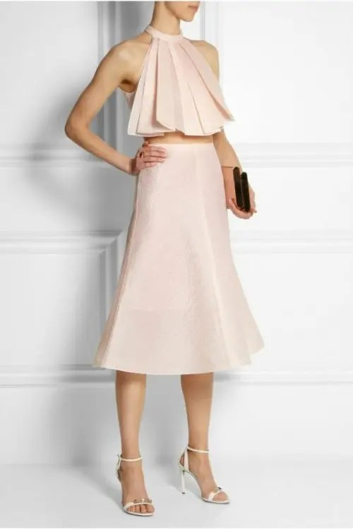 a trendy and bold look in blush with a pleated halter neckline crop top and a midi skirt plus white shoes and a black clutch