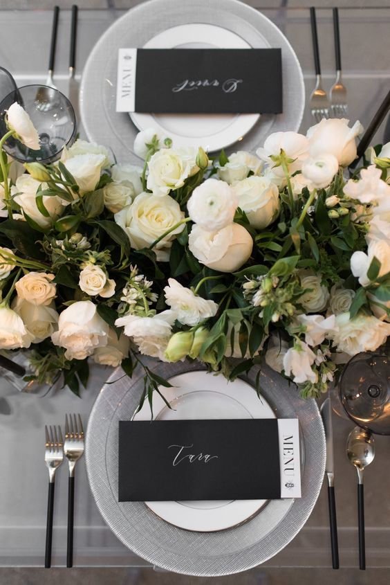 a black and white table setting with black menus, lush white florals, cutlery with black handles and grey chargers