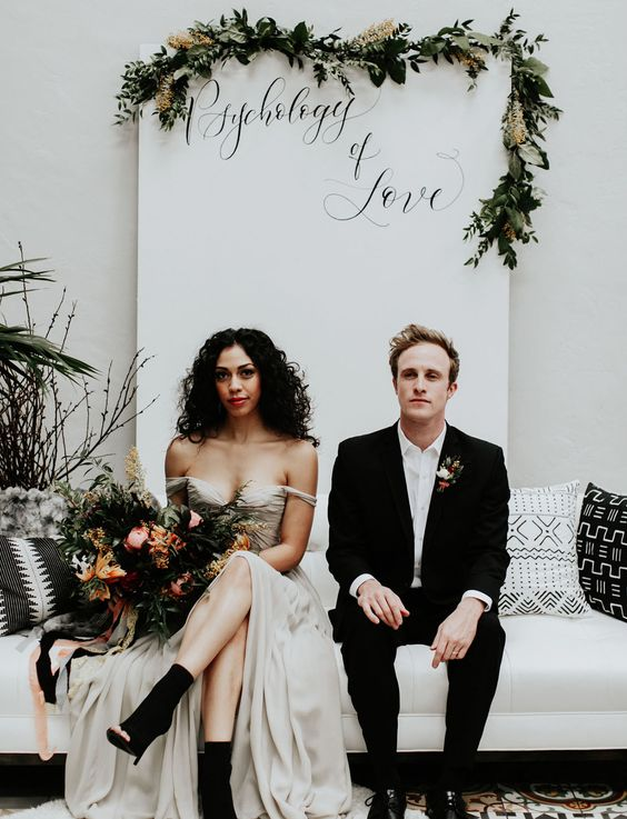 a groom wearing black and white and a bride rocking a neutral gown with black booties
