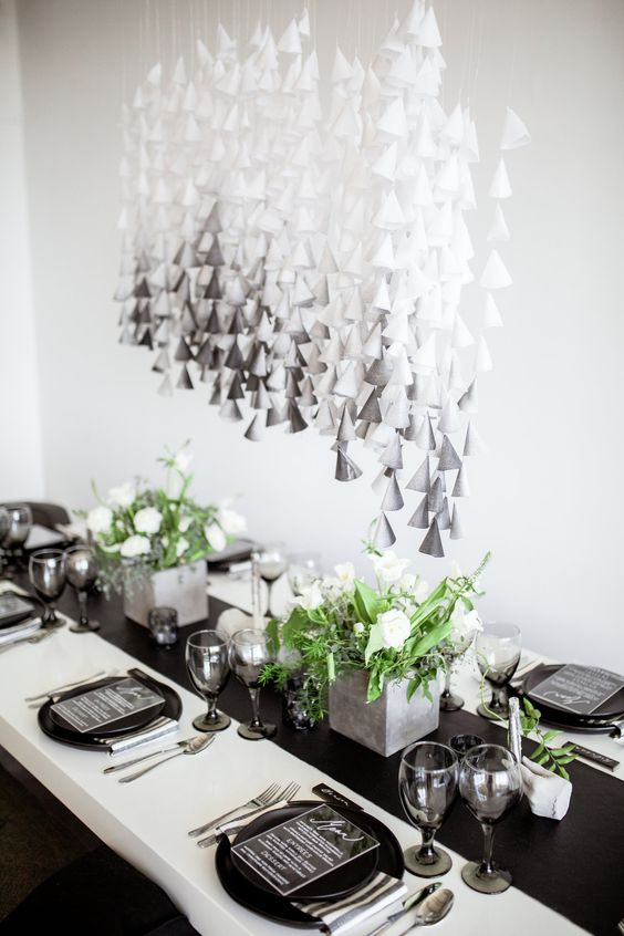 a modern wedding tablescape with black chargers, a runner and concrete planters with greenery and blooms