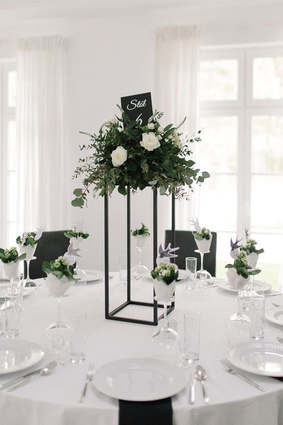 a stylish minimalist wedding tablescape with a tall centerpiece on a black stand, lush white blooms and greenery and black napkins