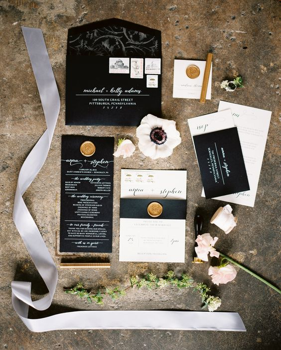 black and white wedding stationery with calligraphy and gold seals for an elegant feel