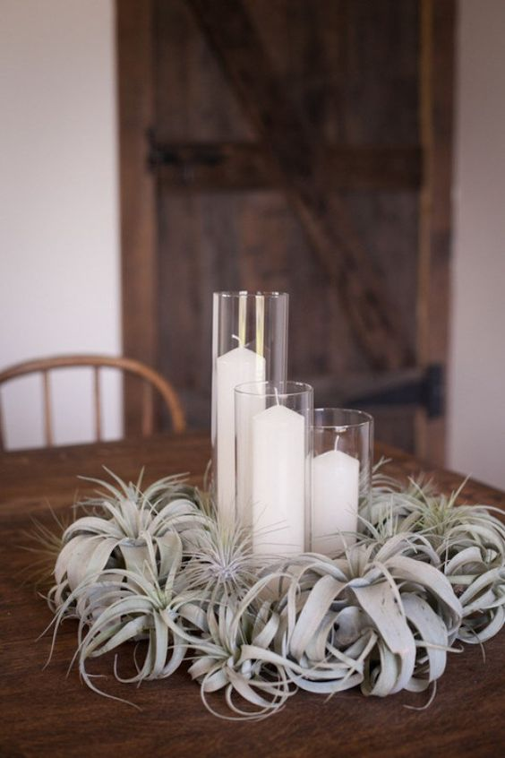 a lush pale air plant wedding centerpiece with pillar candles is a chic idea that is reasy to recreate