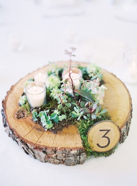 a rustic wedding centerpiece with moss, succulents, candles and with a table number for coziness and a natural feel