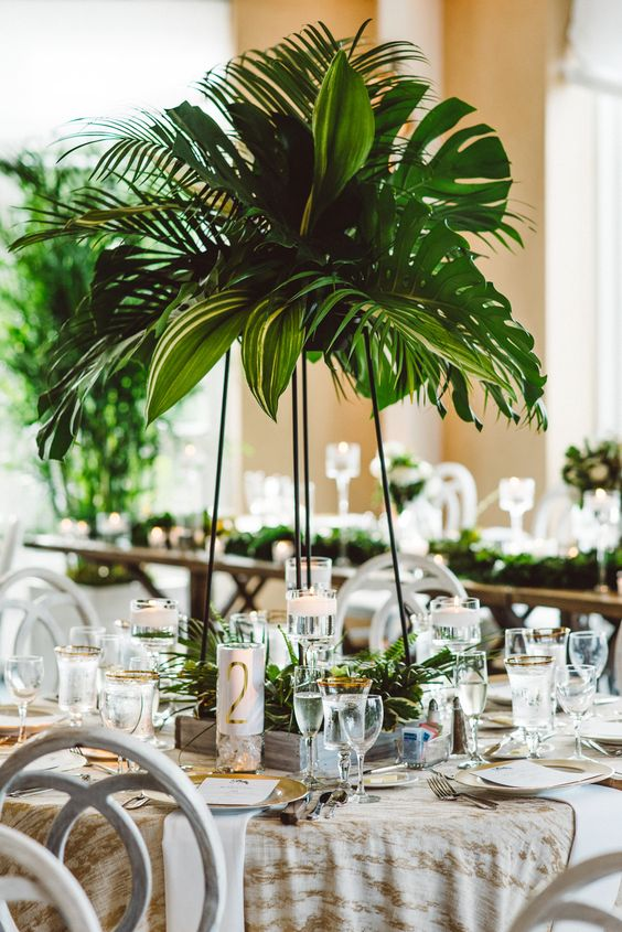 a tall tropical wedding centerpiece with large tropical leaves is a cool and fresh idea for a tropical wedding