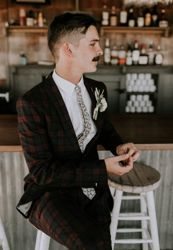 a quirky retro look with a red and black checked suit, a white shirt and a floral tie plus a florla boutonniere