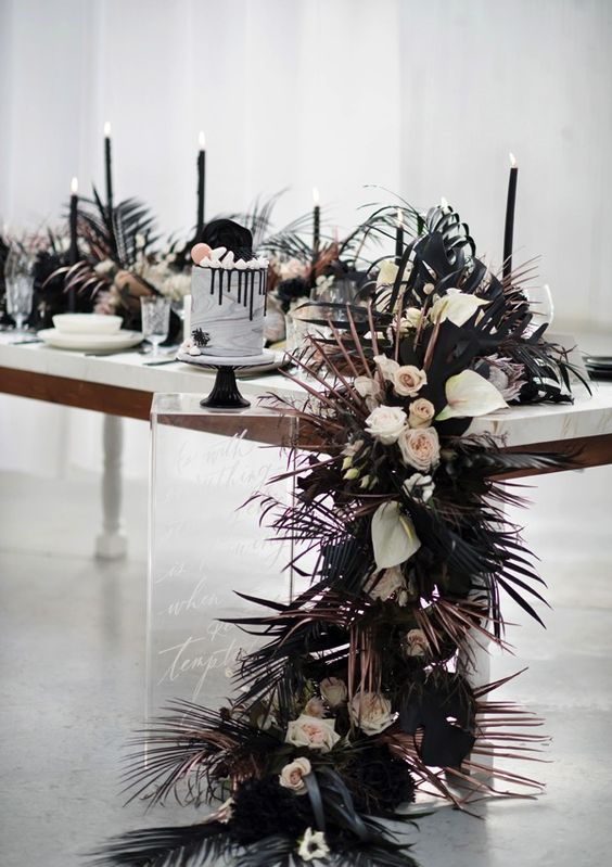 a black and white wedding tablescape with a cascading textural runner, black candles and a marble wedding cake