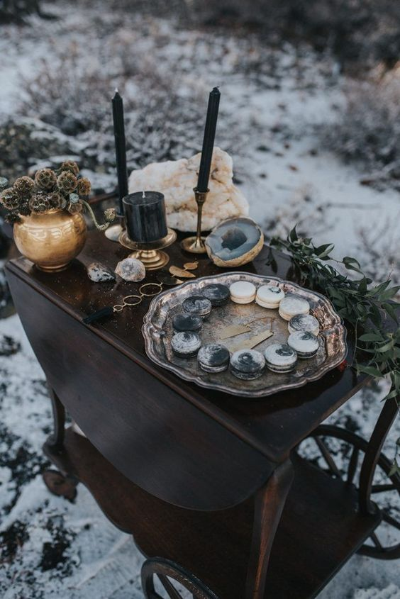 a wedding dessert table with marbleized macarons in white and grey, geodes and black candles