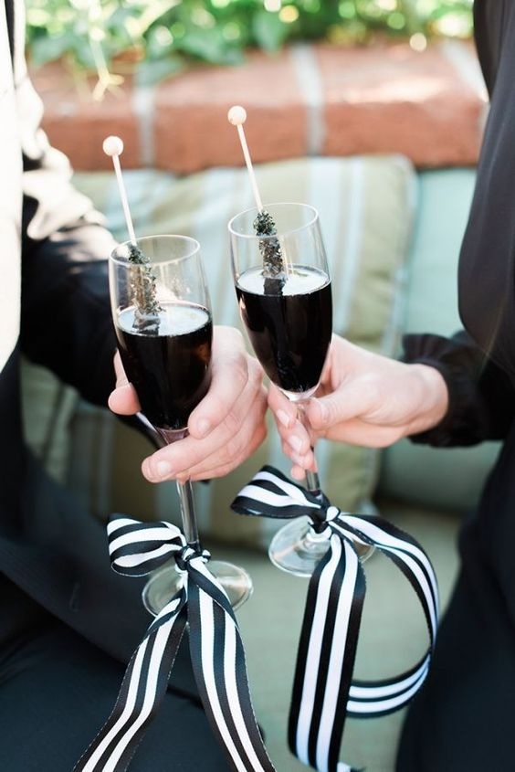 black drinks in glasses with black and white ribbon bows and black sugar rock candies