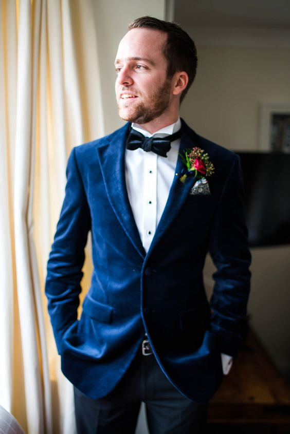 a bright blue velvet suit, a white button down, a black bow tie and a bright floral boutonniere