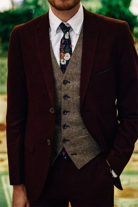 a burgundy velvet suit, a brown tweed waistcoat, a white button down, a moody floral tie for a winter look with a touch of boho