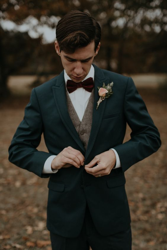 a moody winter look with a teal suit, a brown tweed waistcoat, a burgundy velvet bow tie and a floral boutonniere
