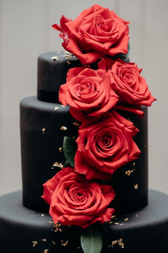 a black wedding cake decorated with red roses and gold leaf is a chic modern idea