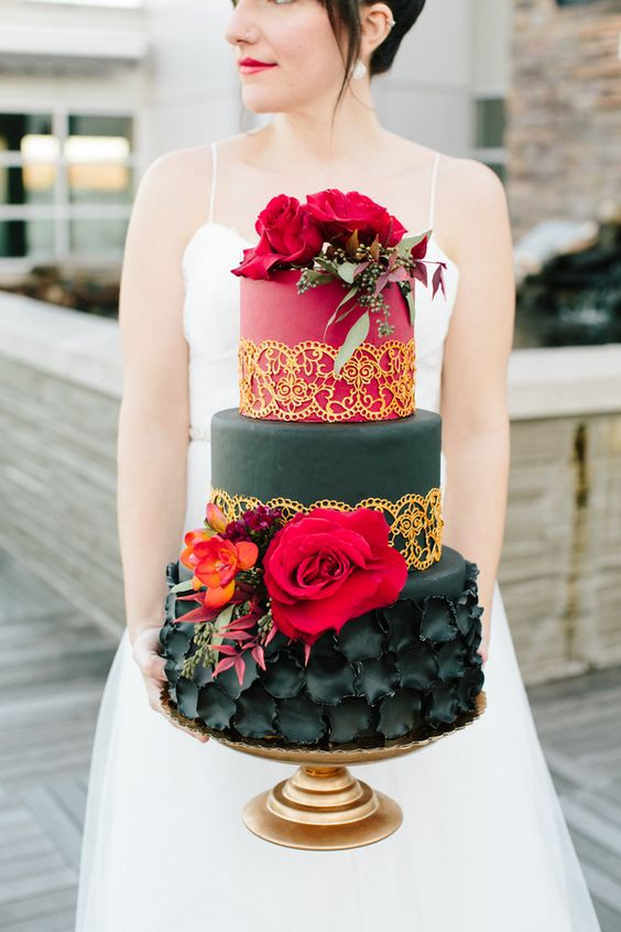 a bold red and black wedding cake with sugar flowers, gold touches, hot red blooms has a wow effect