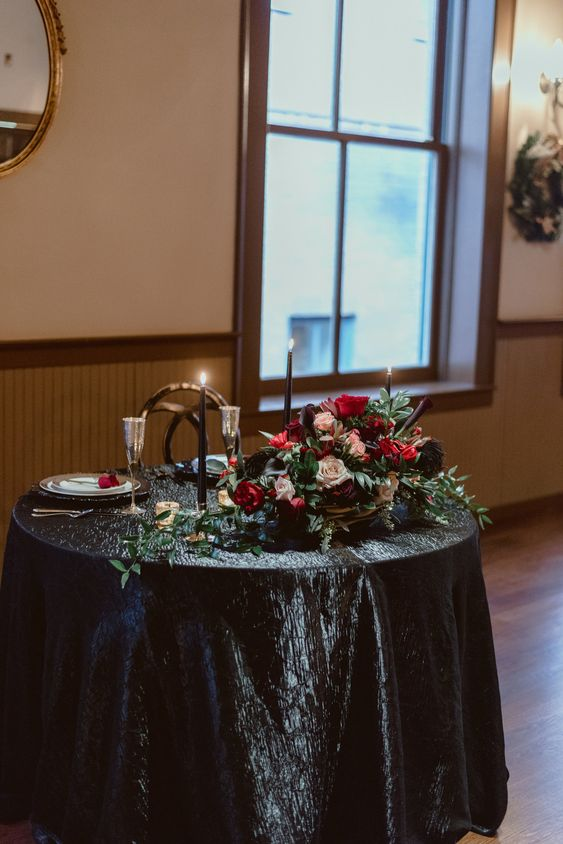 a chic head table with a black tablecloth, black candles in gold candle holders, a lush centerpiece with hot red and black blooms