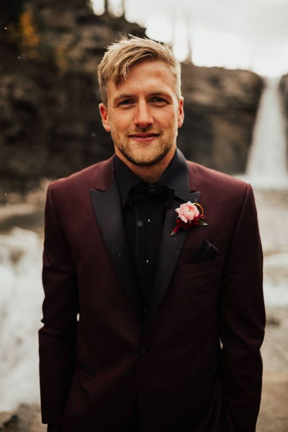 a maroon wedding suit with black lapels, a black shirt and bow tie for a statement wedding look