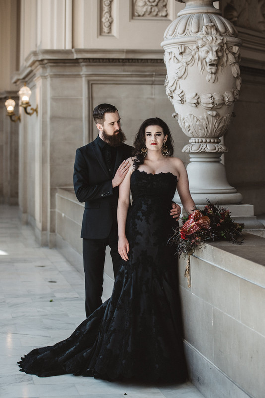 the couple wearing black, the groom in a black suit, shirt and tie, the bride in a black lace strapless wedding dress with a train