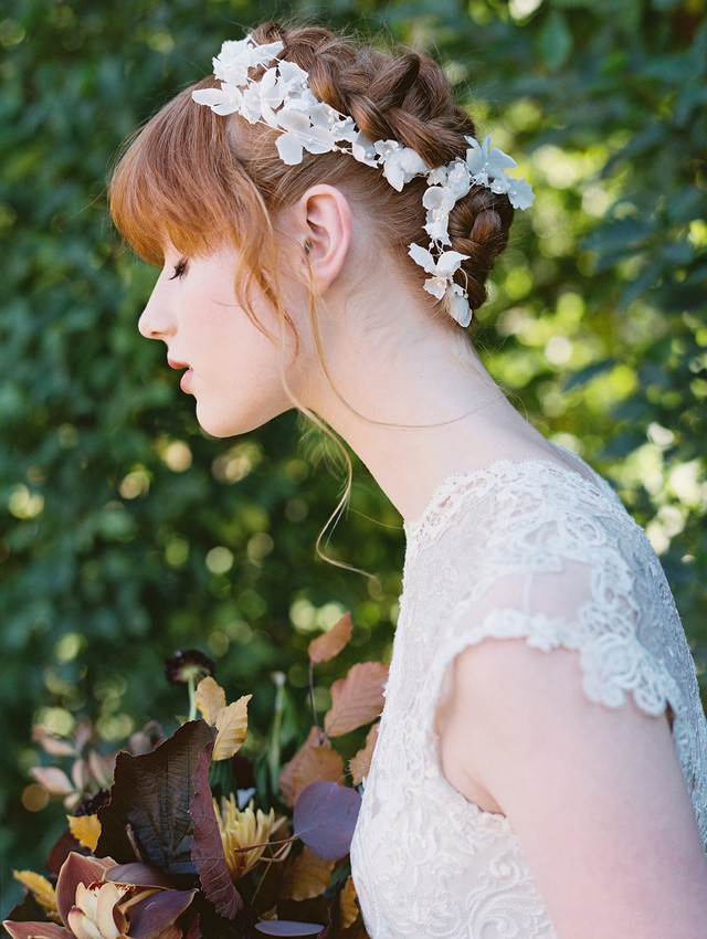 a fully braided updo with lace floral trim and bangs for a subtle and chic bridal look