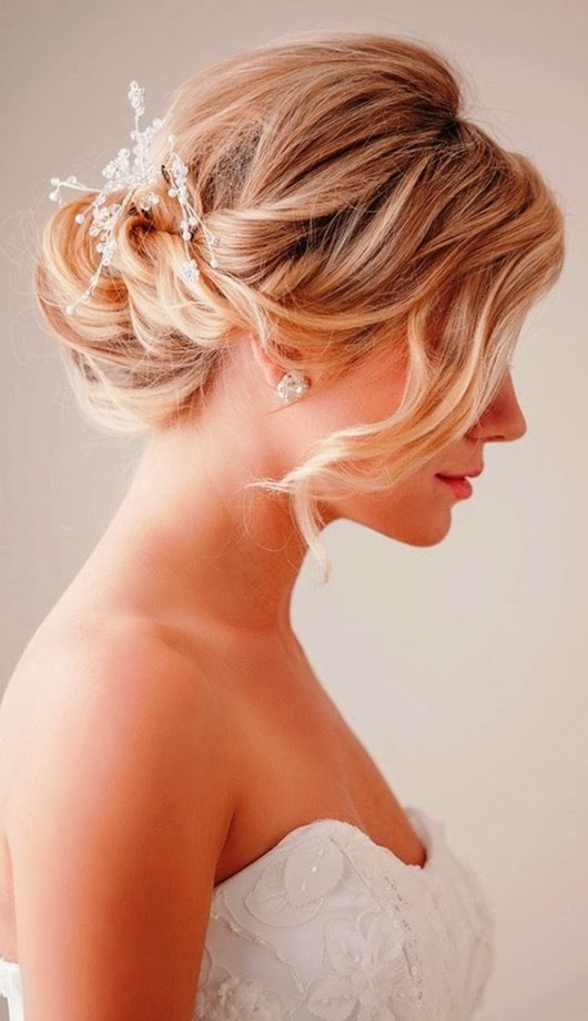 a low twisted chignon with a rhinestone hairpiece and a long bang on one side